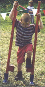 A young lad tries his hand at stiltwalking.