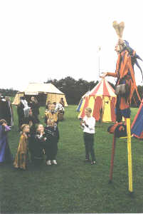 Kris entertaining the children at a medieval wedding balancing a plastic sword on his finger whilst on his stilts.